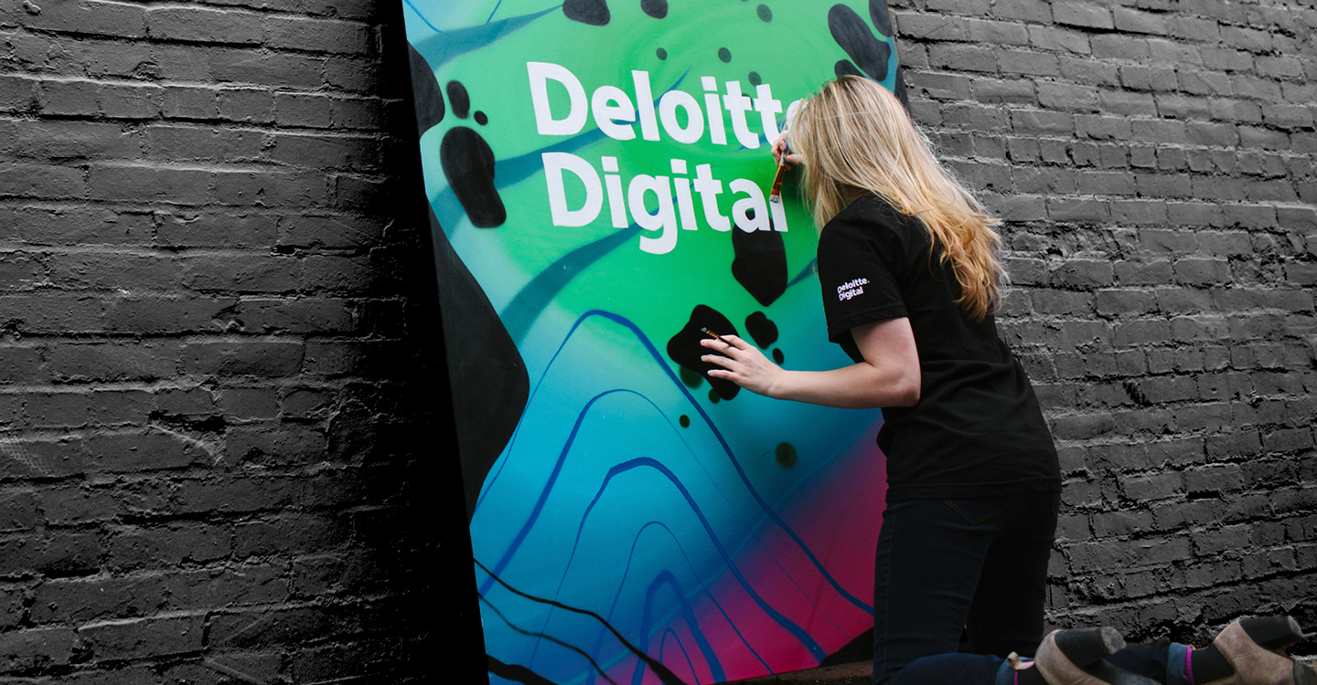 Person painting a Deloitte Digital mural
