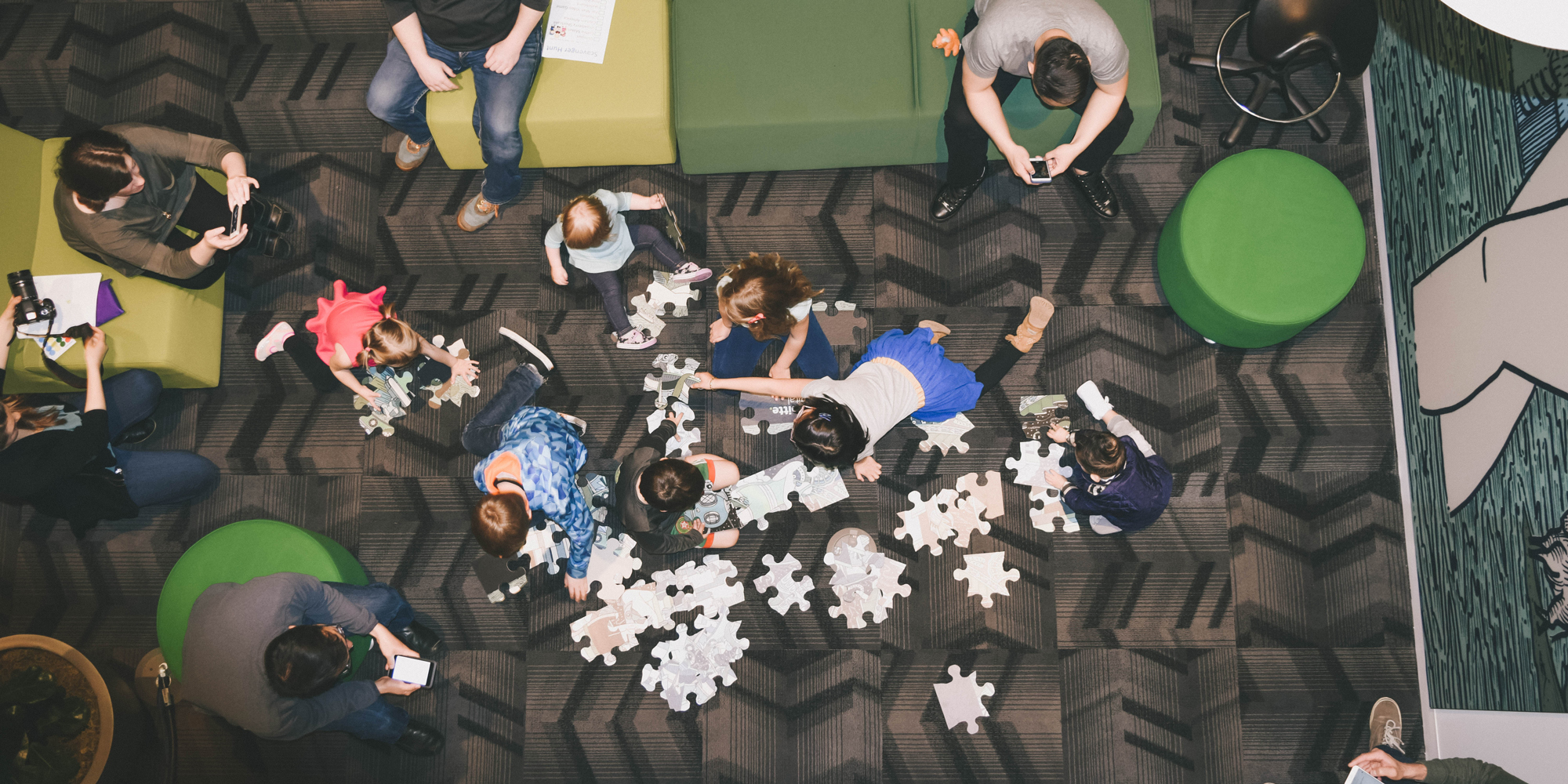 Aerial view of children playing with their parents at work