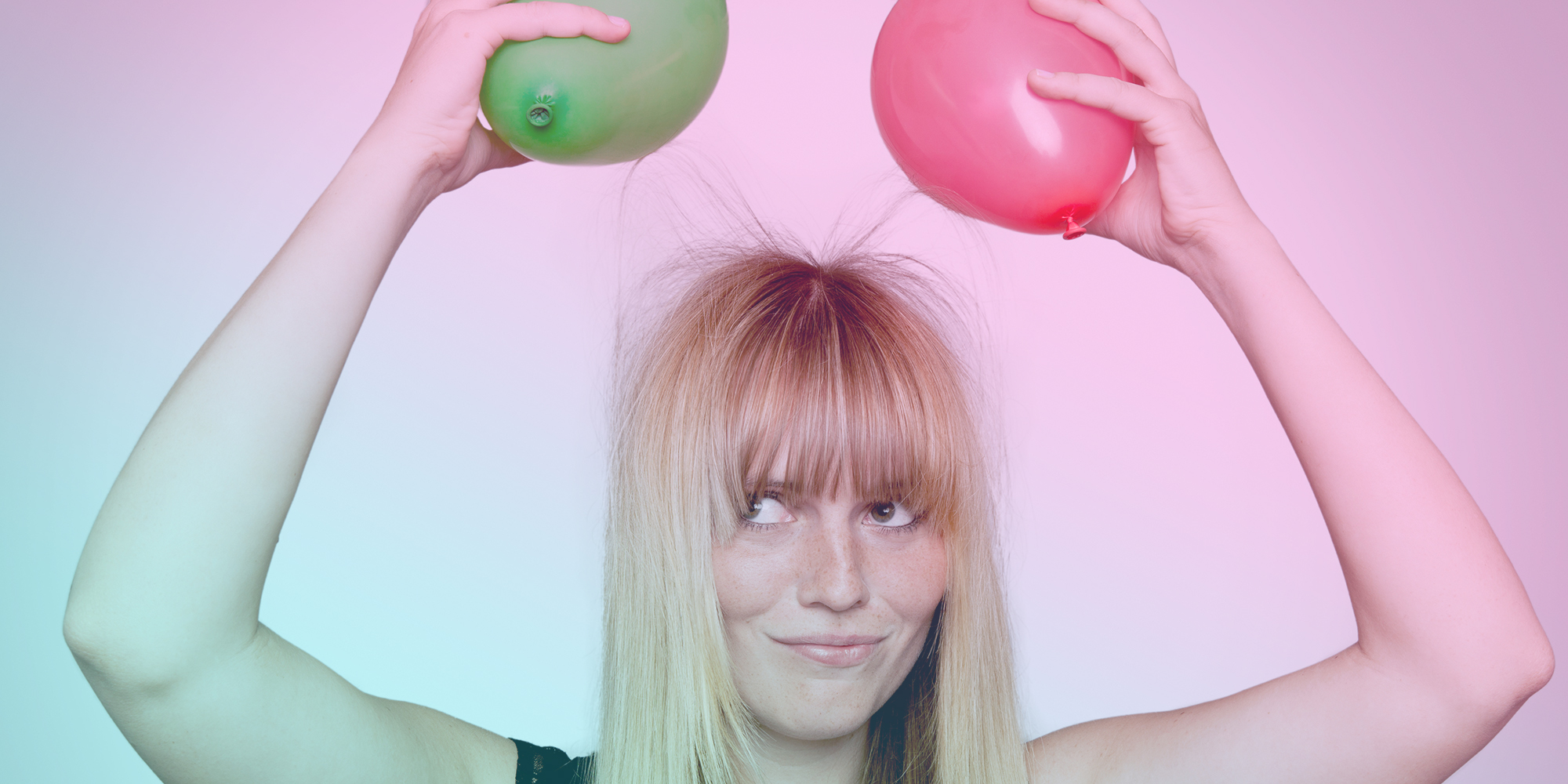 Woman with electrically-charged balloons stuck to hair
