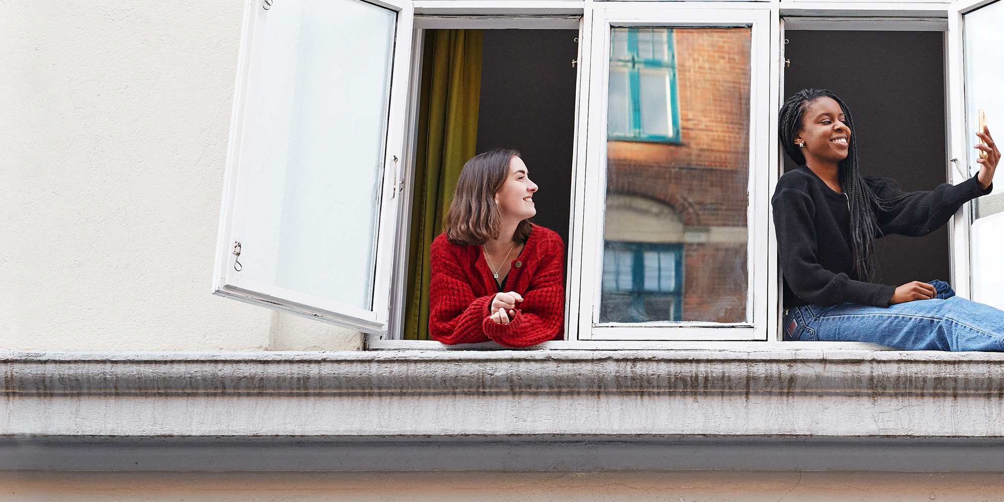 two women hanging out by their window