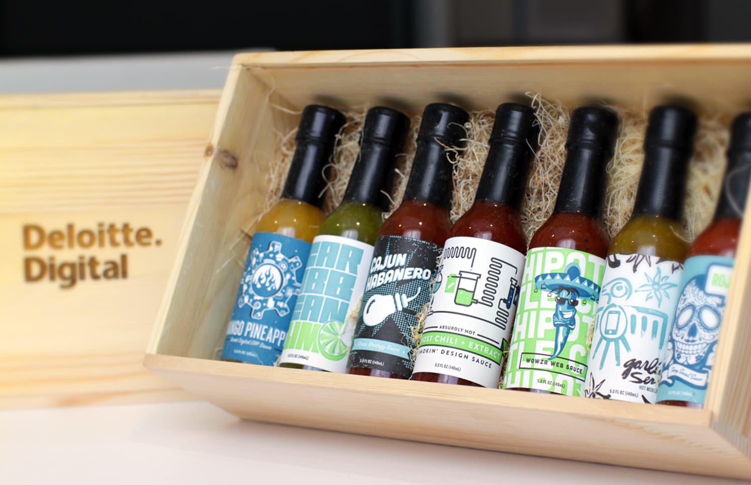 Photo of seven hot sauce bottles with different label designs in a wooden box