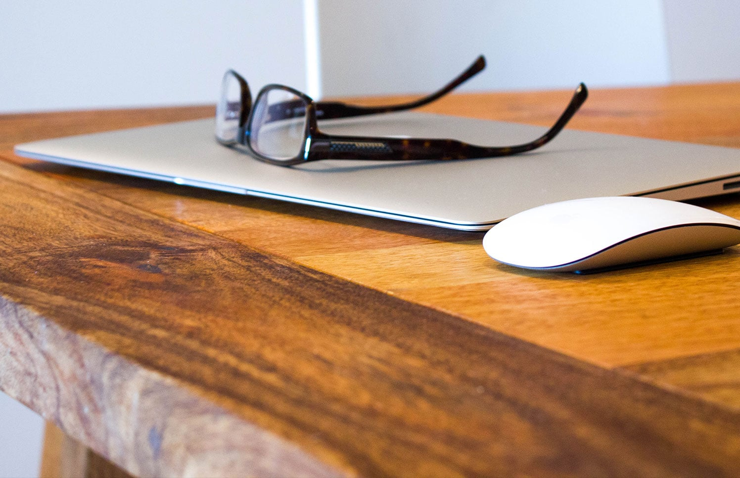 Photo of a laptop, mouse, and glasses on a table
