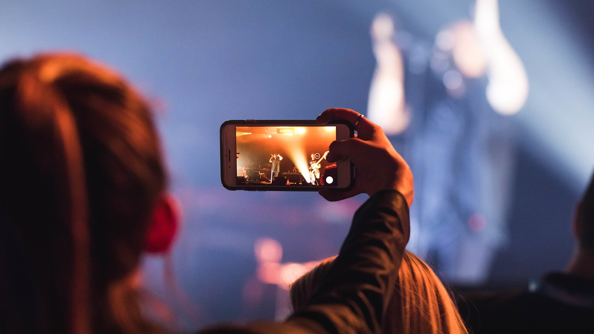 Woman taking photo of concert with phone