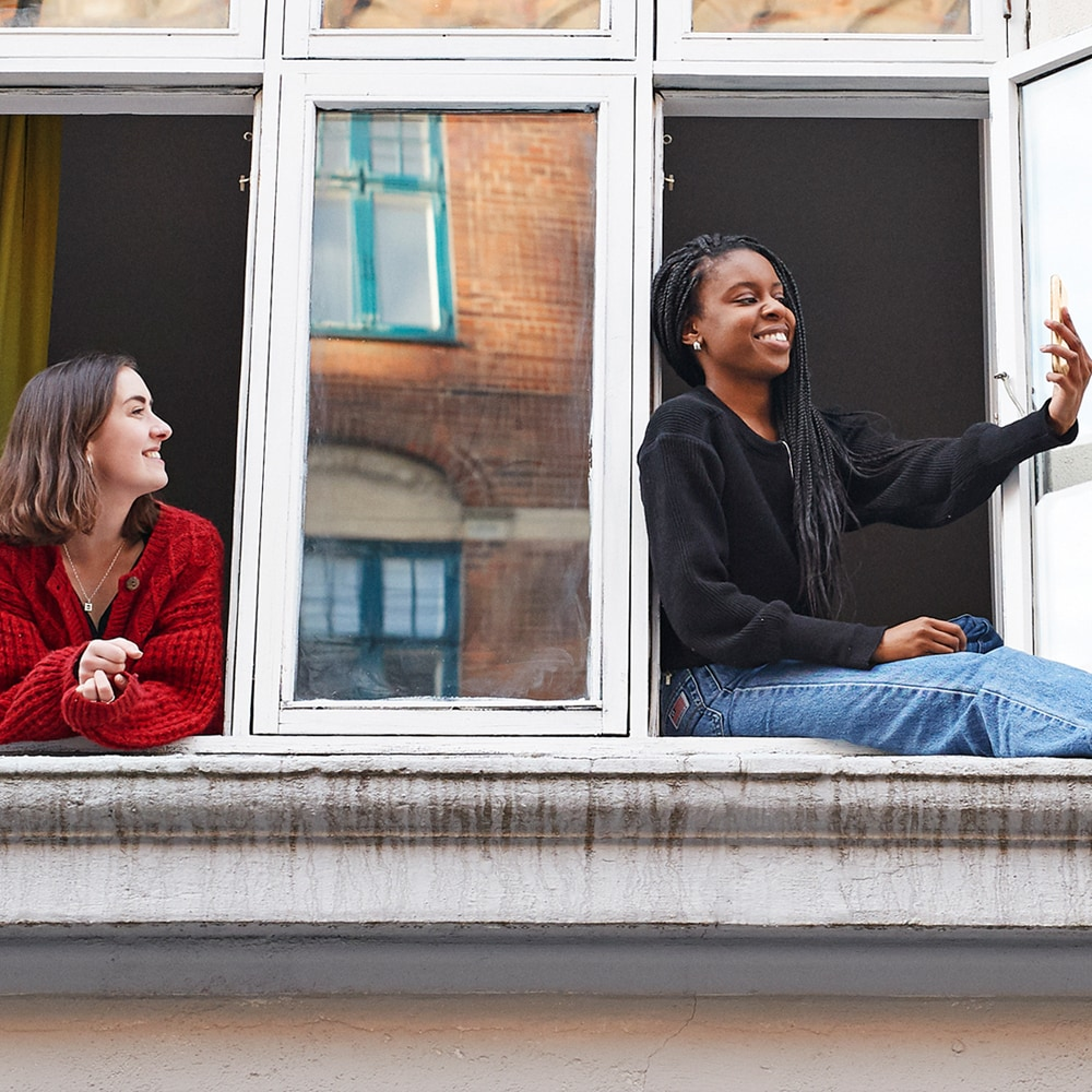 two women hanging out by a window